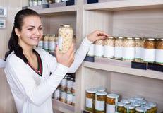 Girl deciding on canned beans. Smiling girl deciding on canned beans in a grocery shop Stock Image