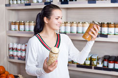 Girl deciding on canned beans. Smiling girl deciding on canned beans at grocery shop Royalty Free Stock Image
