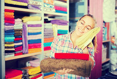 Girl deciding on choice of towels. Smiling customer deciding on the choice of towels in textile shop Royalty Free Stock Photo