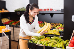 Girl deciding on fruits Stock Images