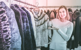Girl deciding on fur jacket. Smiling girl deciding on short coffee-colored fur jacket in women's cloths store Royalty Free Stock Photos