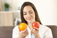 Girl deciding between two fruits. An apple and an orange sitting on a couch in the living room at home Royalty Free Stock Photos
