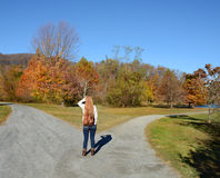 Girl deciding which way to go. Girl with a choice near the forked road. Beautiful autumn day. Colorful fall trees and mountains in the background Royalty Free Stock Photos