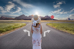 Girl in decision for the right and a wrong way at junction. Woman standing in front of crossing towards the beautiful sunset and idyllic mountain landscape with Royalty Free Stock Photo