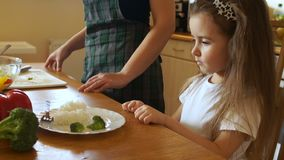 The girl decisively pushes away a plate of food. Looks at the mother and shakes his head, the child refuses to eat