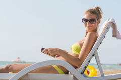 Girl on a deck chair on beach with a smile look in the frame Royalty Free Stock Photos