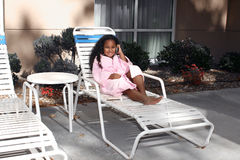 Girl on deck lounge chair. A view of a pretty, multi-racial girl, sitting on a deck or patio lounge chair stock image