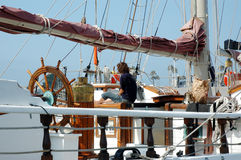 Girl on deck of Tall ship 2. Women sitting on deck of a tall ship royalty free stock photo
