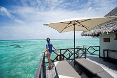 Girl on the deck of water villa. Girl watch towards the sea on the deck of water villa in maldives resort stock photography