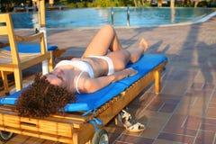 Girl on deckchair. Woman on the deckchair near the pool Royalty Free Stock Image