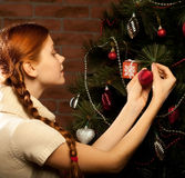 Girl decorate the Christmas tree. In a house interior Stock Photography