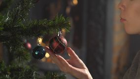 Girl decorate Christmas tree in a house. holiday celebration. season`s greetings. Hands close-up stock video