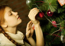 Girl decorate the Christmas tree Royalty Free Stock Photo