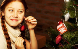 Girl decorate the Christmas tree Royalty Free Stock Photos