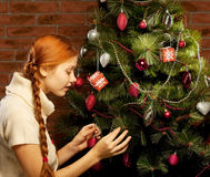 Girl decorate the Christmas tree Stock Image