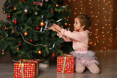 Girl decorate the Christmas tree in a house interior Royalty Free Stock Photos