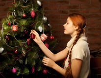 Girl decorate the Christmas tree Stock Photo