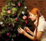 Girl decorate the Christmas tree Stock Photos