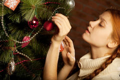 Girl decorate the Christmas tree Royalty Free Stock Image