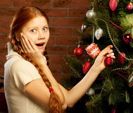 Girl decorate the Christmas tree in a house interior Royalty Free Stock Images