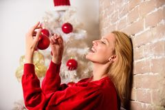 Girl decorate christmas tree with ornaments. Waiting for christmas. Girl wear red dress sit near christmas tree. Woman. Happy hold christmas ball ornament royalty free stock photos