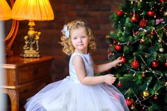 Girl decorate a festive Christmas tree. Beautiful little girl in a dress decorates with balls festive Christmas tree Royalty Free Stock Image