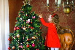 Girl decorate a festive Christmas tree. Beautiful little girl in a dress, standing on an armchair and decorating a festive Christmas tree Stock Image