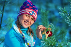 Girl decorate tree. Girl decorate cristmass tree in forest Stock Photo