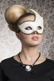 Girl with decorated mask. Close-up portrait of elegant woman with classic blonde hair-style, necklace and cute decorated mask. Mysterious beautiful woman Stock Photo