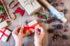 Girl decorates Christmas gift, ties red bow Stock Photography