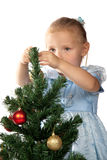 Girl decorates a Christmas tree Stock Images