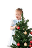 Girl decorates a Christmas tree Royalty Free Stock Images