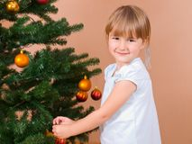 Girl decorates Christmas tree Stock Images