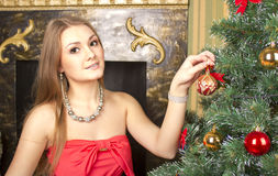 Girl decorates the Christmas tree Stock Images