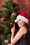 Girl decorates the Christmas tree. Young attractive girl in a Christmas cap decorates a Christmas tree Stock Photos