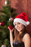 Girl decorates the Christmas tree. Young attractive girl in a Christmas cap decorates a Christmas tree Stock Images