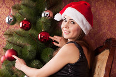Girl decorates the Christmas tree. Young attractive girl in a Christmas cap decorates a Christmas tree Royalty Free Stock Photo