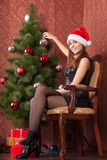Girl decorates the Christmas tree. Young attractive girl in a Christmas cap decorates a Christmas tree Royalty Free Stock Image