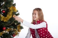 Girl decorates the Christmas tree Stock Image