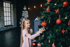 Girl decorates the Christmas tree Stock Photography