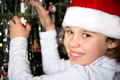 Girl decorates Christmas tree Royalty Free Stock Photos
