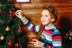 Girl decorates Christmas tree Stock Photo