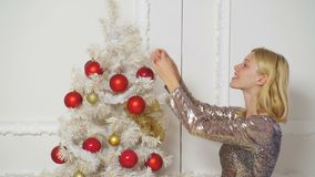Girl decorates Christmas tree. Merry Christmas and Happy Holidays. Happy girl decorate the Christmas tree indoors. The stock footage