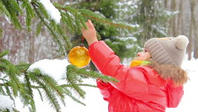 Girl decorates a Christmas tree. In the park stock video