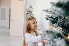 Girl decorates the Christmas tree Royalty Free Stock Images