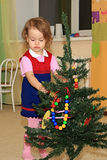 Girl decorates a conifer. A little girl decorates a conifer toys Royalty Free Stock Photo