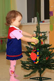 Girl decorates a conifer. A little girl decorates a conifer toys Stock Photo