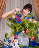 The girl decorates fur-tree branches Stock Images