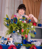 The girl decorates fur-tree branches Stock Photos