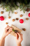 Girl decorates the gift in the Rustic style, hands in the shot. Royalty Free Stock Image